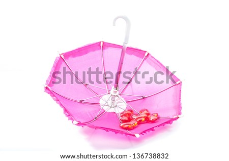 Pretty pink parasol standing open and upside down on a white background with a collection of red translucent romantic hearts for Valentine or celebrating an anniversary - stock photo