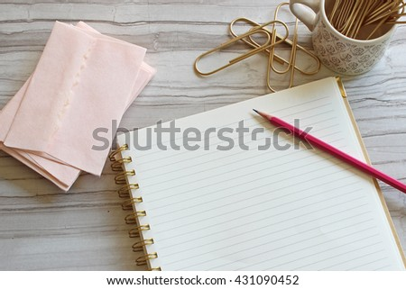 Pretty pink stationary, pencil and gold paperclips with blank notebook page over head view with room for copy.  - stock photo