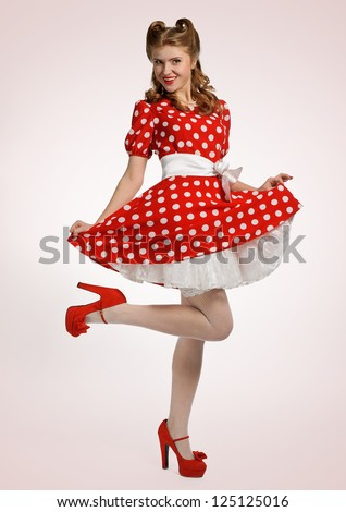 pretty pinup model in a red and white polka dot dress stock photo