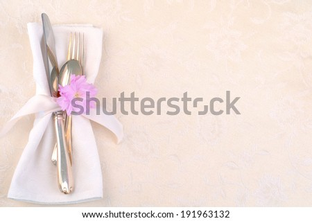 Pretty Place Setting with fork, knife, spoon, napkin, cherry blossom on cream damask tablecloth with room or space for copy, text.  Horizontal, above - stock photo