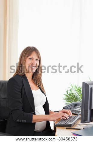 Pretty pregnant female working with a computer at the office - stock photo