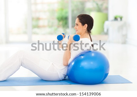 pretty pregnant woman exercising with dumbbells at home
