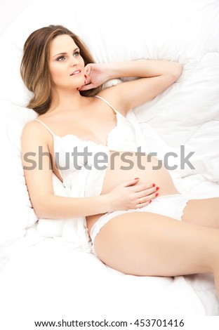 Pretty pregnant woman in a bed - stock photo