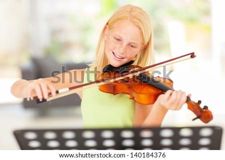 pretty preteen girl practicing violin at home - stock photo