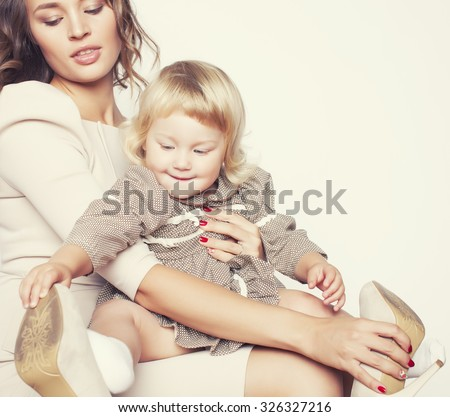 pretty real fashion mother with cute blond little daughter close up isolated - stock photo