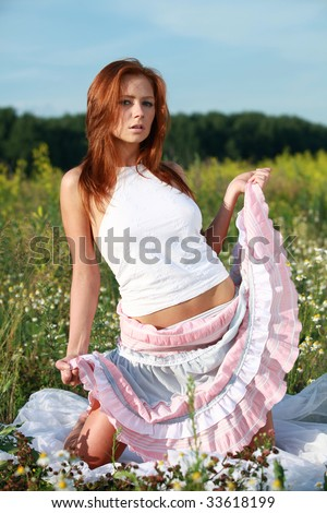 Pretty red girl in a long skirt in nature - stock photo