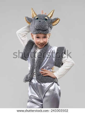 Pretty red-haired girl in a cow costume shows the horns - stock photo