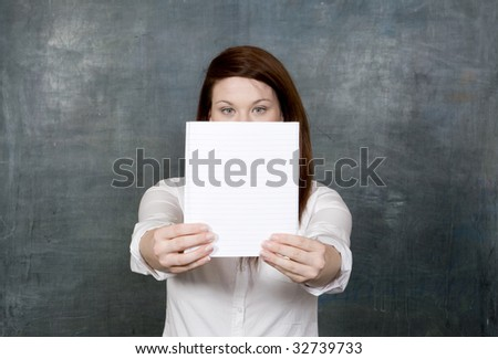 Pretty red head student holds blank notebook