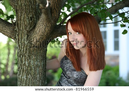 pretty red head young teen girl by tree with freckles - stock photo