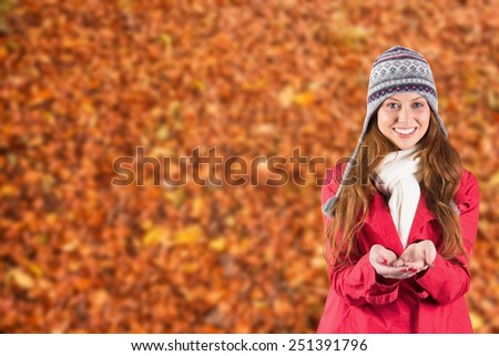Pretty redhead in warm clothing against autumn leaves on the ground - stock photo
