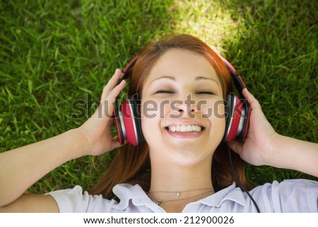 Pretty redhead lying on grass listening to music on a sunny day - stock photo