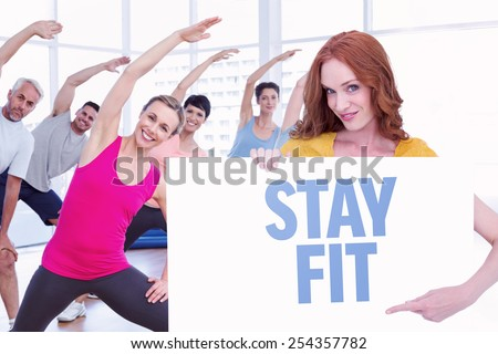 Pretty redhead showing a poster against stay fit - stock photo