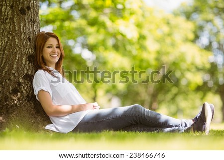 Pretty redhead sitting and smiling in park on a sunny day - stock photo