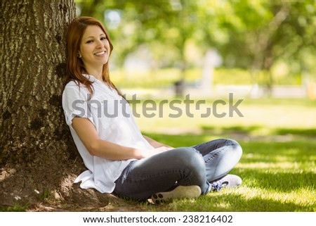 Pretty redhead sitting in casual clothing in park on a sunny day - stock photo