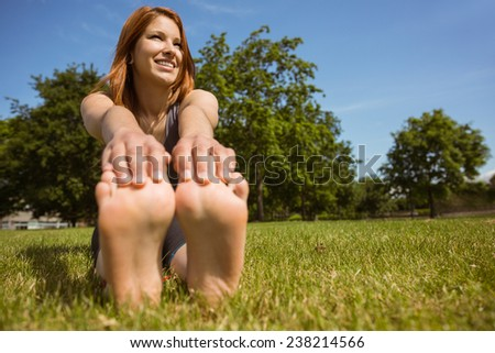 Pretty redhead smiling stretching in park on a sunny day - stock photo
