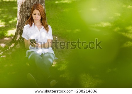 Pretty redhead text messaging on her phone in park on a sunny day - stock photo
