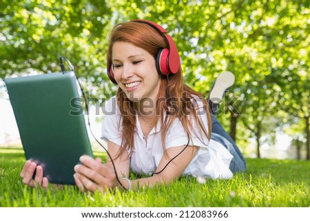 Pretty redhead using her tablet pc while listening to music in the park on a sunny day - stock photo