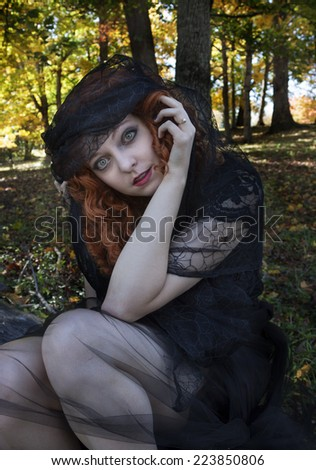 Pretty redhead wearing black dress and black veil in forest - stock photo