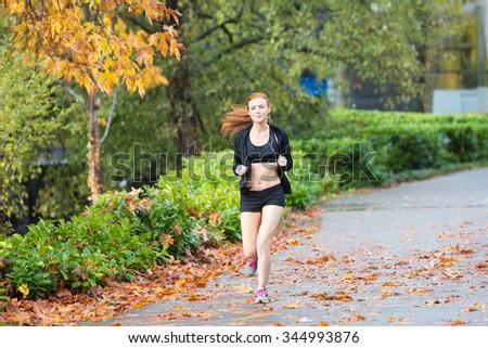 Pretty redhead woman jogging outside - stock photo