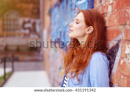 Pretty redhead woman taking a moment to herself leaning back against a graffiti covered brick wall with her eyes closed and a serene expression - stock photo