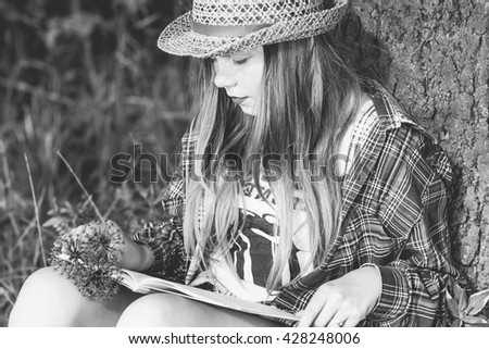 Pretty relaxed young woman reading a book at the lawn with sun shining - stock photo