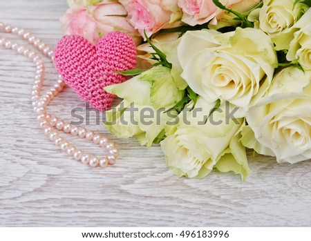 pretty roses on the wooden background with knitting heart