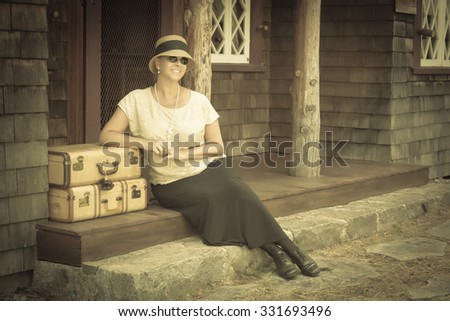 Pretty 1920s Dressed Girl Next To Suitcases on Porch with Vintage Effect Added.