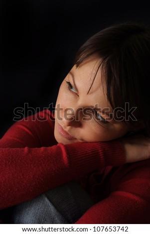 Pretty sad Caucasian girl sitting on a dark background - stock photo