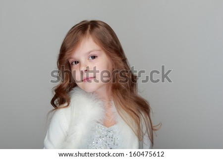 Pretty sad little child with brunette curly long hair on gray background - stock photo
