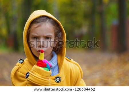 Pretty sad little girl in yellow coat with hood put finger to lips in city autumn park.