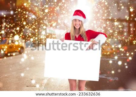Pretty santa girl holding poster against blurry new york street - stock photo