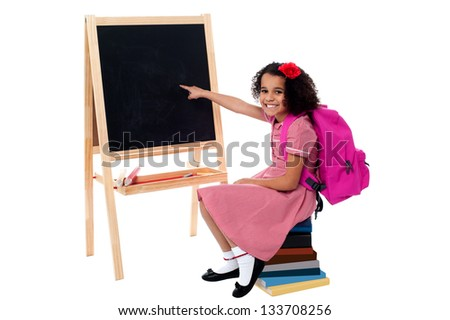 Pretty school girl sitting on stack of books and pointing towards blank chalkboard. - stock photo
