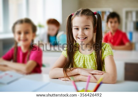 Pretty schoolgirl looking at camera by desk - stock photo