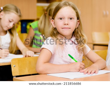 pretty schoolgirl looking at camera during lesson