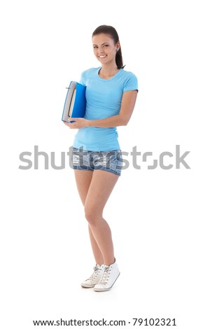 Pretty schoolgirl wearing shorts and t-shirt, smiling, holding folder.? - stock photo