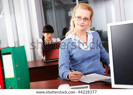 Pretty secretary doing paperwork in the office