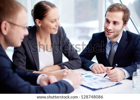 Pretty secretary looking at one of partners during paperwork at meeting
