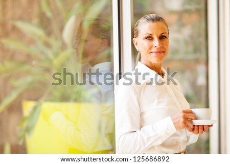 pretty senior female corporate executive in office with coffee - stock photo