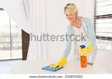 pretty senior housewife wiping table at home - stock photo