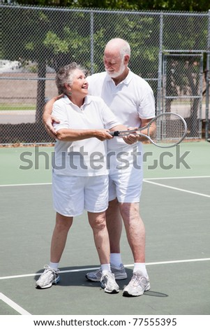 Pretty senior woman gets a tennis lesson from her handsome husband. - stock photo