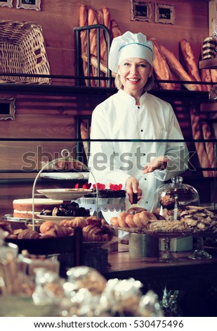 Pretty senior woman selling fresh pastry and baguettes in local bakery