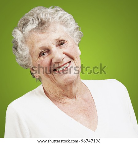 pretty senior woman smiling against a green background - stock photo