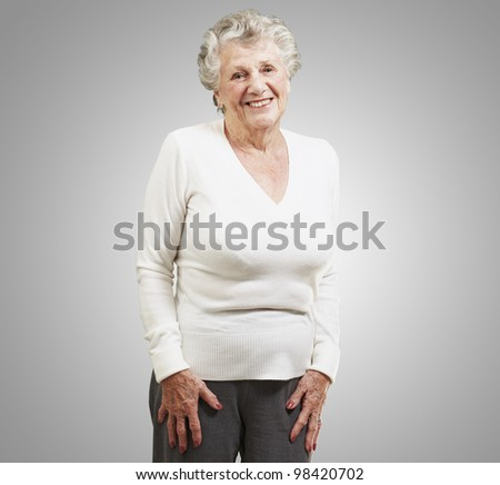 pretty senior woman smiling against a grey background - stock photo