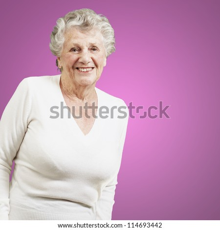 pretty senior woman smiling against a pink background - stock photo