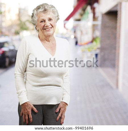 pretty senior woman smiling against a street background - stock photo