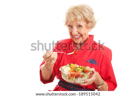 Pretty senior woman stays fit and eats healthy salad.  Isolated on white. - stock photo