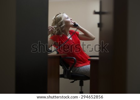 Pretty sexual blonde woman secretary with curly hair in red blouse sitting in private cabinet at table speaking by phone view from door, horizontal picture - stock photo