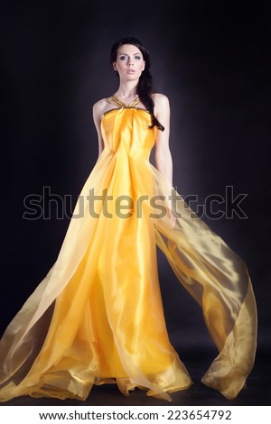 Pretty sexy girl full length posing in a nice yellow dress over black background, series photo. Fashion studio shot of beautiful woman with makeup and hairstyle wearing evening dress - stock photo