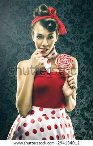 Pretty sexy woman in red vintage polka dot dress - with lollipop - stock photo