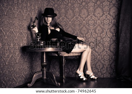 Pretty sexy woman is sitting and calling on an old telephone. Retro style
